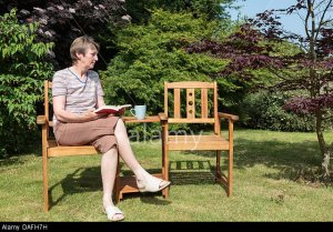 DAFH7H Senior woman widow looking sad sitting alone beside an empty seat in a sunny garden in summer. UK, Britain